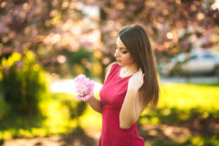 Beautiful girl posing to the photographer against the background of blooming pink trees. Spring. Sakura. Royalty Free Stock Photo
