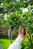 Beautiful girl posing in wedding dress with tropical leaves stock images