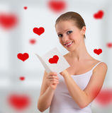 Beautiful girl with a postcard valentine. On abstract background with red hearts stock images
