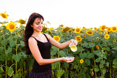 Beautiful girl pours sunflower oil from the jug Royalty Free Stock Images