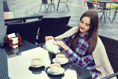 Beautiful girl pours tea from  teapot into a cups Royalty Free Stock Photography
