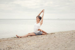 Beautiful girl practicing yoga on the beach near the sea. Sits on a twine, does a stretching. royalty free stock photography