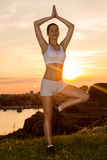 Beautiful girl practicing yoga in sunset Royalty Free Stock Photo