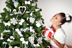 Beautiful girl with present near the Christmas tree Royalty Free Stock Image