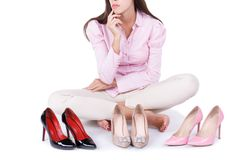 Young girl presents three modern pairs of high-heeled shoes isolated on a white background. Stock Photography