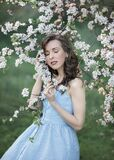 A beautiful girl presses a branch of a blooming Apple tree
