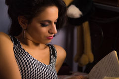 Beautiful girl with professional make-up reading a book. A close up shot a beautiful young girl with red lipstick and a professional make up in incandescent royalty free stock image