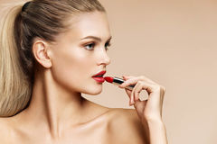 Beautiful girl in profile applying red lipstick. Royalty Free Stock Photography