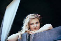 Beautiful girl props up on the wooden handrail Royalty Free Stock Image