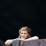 Beautiful girl props up on the wooden handrail Stock Image