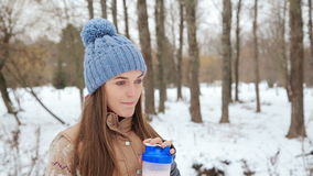 Beautiful girl protein drink in the winter park stock footage