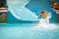 Beautiful girl pulls off the slides at the water park Stock Image