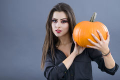 Beautiful girl with pumpkin in the studio isolated on gray backg Stock Image