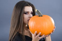 Beautiful girl with pumpkin in the studio isolated on gray backg Royalty Free Stock Photography