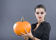 Beautiful girl with pumpkin in the studio isolated on gray backg Stock Photos