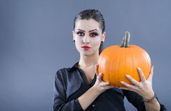 Beautiful girl with pumpkin in the studio isolated on gray backg Royalty Free Stock Images