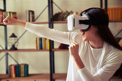 Beautiful girl punch someone playing with VR headset Royalty Free Stock Photography
