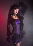 Beautiful girl in purple and black gothic outfit. Beautiful girl in purple and black Victorian outfit holding umbrella, studio shot on black background royalty free stock image