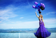 Beautiful girl in the purple dress with balloons Stock Photography