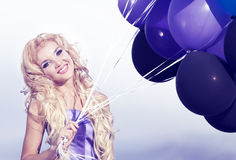 Beautiful girl in the purple dress with balloons. In the background sky Stock Photos