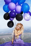 Beautiful girl in the purple dress with balloons Royalty Free Stock Photos