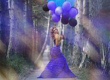 Beautiful girl in the purple dress with balloons. In the background sky Stock Photo