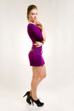 Beautiful girl in purple dress and black shoes. Studio shot stock image