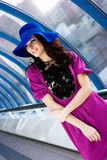 Beautiful girl in purple dress and blue hat. Brunette girl in purple dress posing in the corridor Royalty Free Stock Images