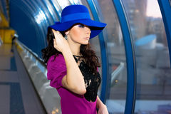 Beautiful girl in purple dress and blue hat. Brunette girl in purple dress posing in the corridor Stock Photos