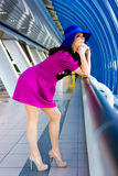 Beautiful girl in purple dress and blue hat Royalty Free Stock Images