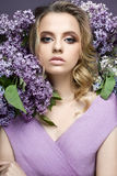 Beautiful girl in a purple dress and a bouquet of lilacs. The model is in an image of spring. The photo was taken in a studio Royalty Free Stock Images