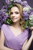 Beautiful girl in a purple dress and a bouquet of lilacs. The model is in an image of spring. The photo was taken in a studio Royalty Free Stock Image