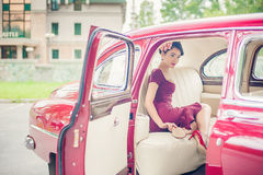 Beautiful girl in purple dress posing inside cherry retro car Stock Image