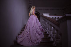 Beautiful girl in a purple dress. Beautiful, young, blond in a luxurious, purple, dress with a long train. Fairy Photo. Creative toning. Queen goes on vintage royalty free stock image