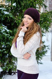 Beautiful girl in a purple knitted winter hat and scarf and knit Royalty Free Stock Photos
