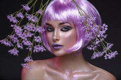Beautiful girl in purple wig. Beautiful young woman in purple wig with artistic violet lipstick and eye makeup with pink sparkles. Beauty shot on black Stock Photo