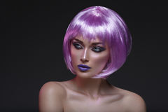 Beautiful girl in purple wig. Beautiful young woman in purple wig with violet makeup with pink sparkles. Beauty shot on black background Stock Photos