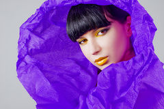 Beautiful girl in purple wrapping paper Royalty Free Stock Photo