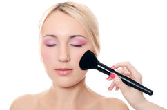 Beautiful girl put the makeup on the face Stock Photos