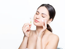 Beautiful girl puts a cream on the face and inhales the fragranc Royalty Free Stock Photography