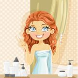 Beautiful girl puts eye cream from a small tube in the Royalty Free Stock Images
