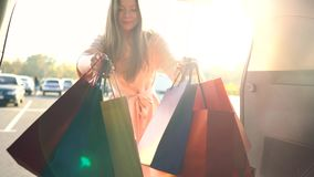 Beautiful girl puts shopping bags in the trunk of a car and leaves, intending to drive away. Shopping concept stock video footage