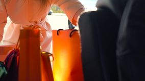 Beautiful girl puts shopping bags in the trunk of a car and leaves, intending to drive away. Slow motion. stock footage