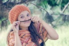 Beautiful girl putting braid's tail end like moustache. Beautiful girl with hairdo putting braid's tail end like moustache stock photography