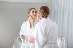 Beautiful girl putting cream on her face in bathroom Stock Photography