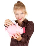 Beautiful girl putting five euro in piggy bank Royalty Free Stock Photography