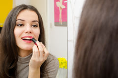 Beautiful girl putting lipstick in front of the mirror Royalty Free Stock Images