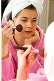 Beautiful girl putting on makeup in the mirror royalty free stock images