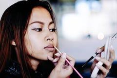 Beautiful girl putting makeup. Portrait of beautiful girl putting makeup Stock Images