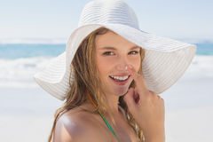 Beautiful girl putting spf on nose on the beach smiling at camera Royalty Free Stock Image